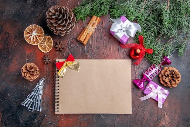 Vista dall'alto un quaderno con fiocchi piccoli rami di pino con coni e giocattoli per alberi di natale cannella fette di limone essiccate anice su sfondo rosso scuro