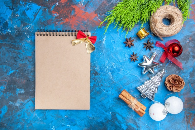 Top view a notebook with little bow straw thread xmas tree toys anise seeds cinnamon sticks on blue-red background