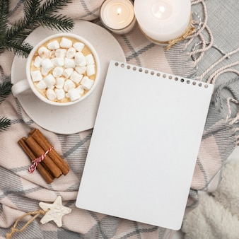 Top view of notebook with mug of marshmallows and cinnamon