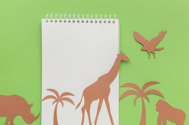 Top view of notebook with paper animals for animal day