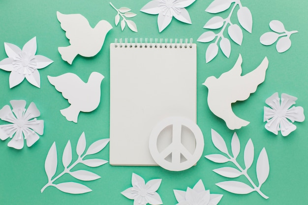 Top view of notebook with paper doves and peace sign