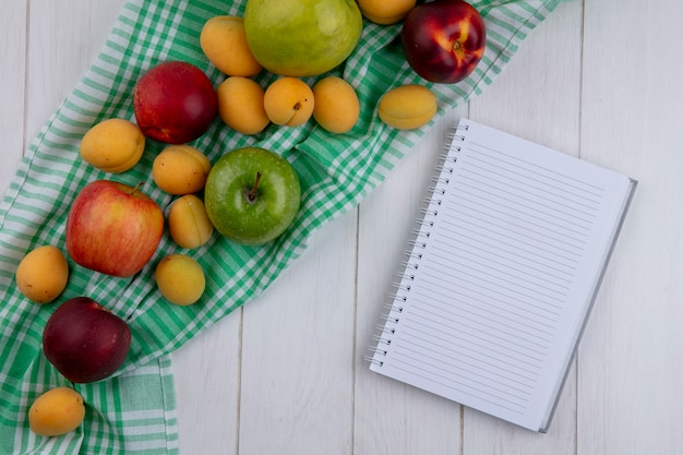 Top view of notebook with peaches apples and apricots on a checkered towel on a white surface