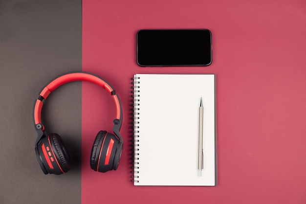 Top view of notebook with pen smartphone and headphone