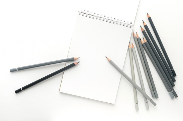 Top view, notebook with pencils on white.