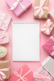Top view of notebook with pink gifts