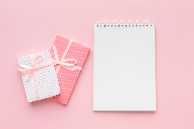 Top view of notebook with pink presents