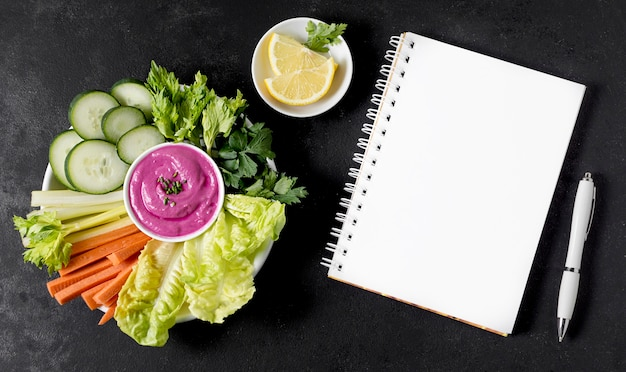 Top view of notebook with pink sauce and vegetables