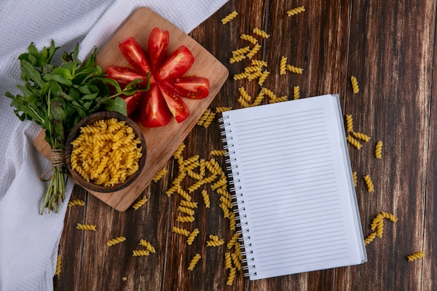 Top view of notebook with raw pasta in a bowl with slicing tomato slices on a cutting board with a bunch of mint on a wooden surface