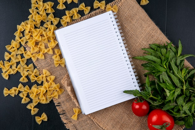 Top view of notebook with raw pasta tomatoes and a bunch of mint on a beige napkin
