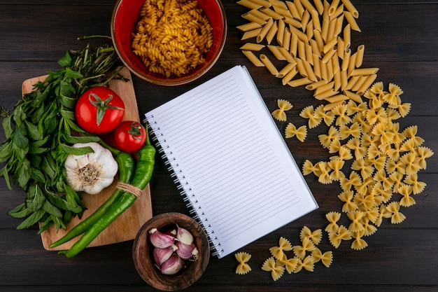 Top view of notebook with raw pasta tomatoes garlic with chili pepper and mint on a cutting board on a wooden surface