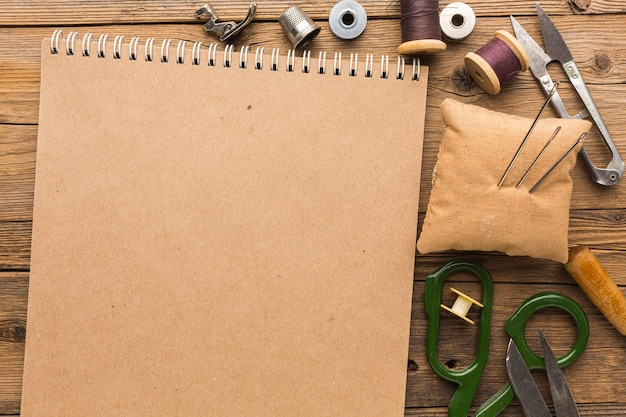 Top view of notebook with scissors and thread