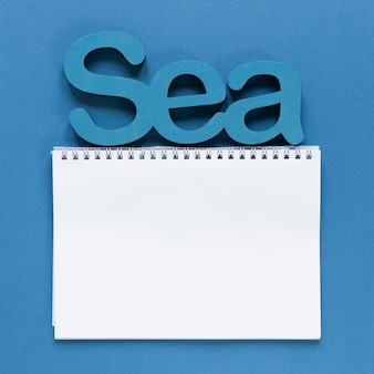 Top view of notebook with sea
