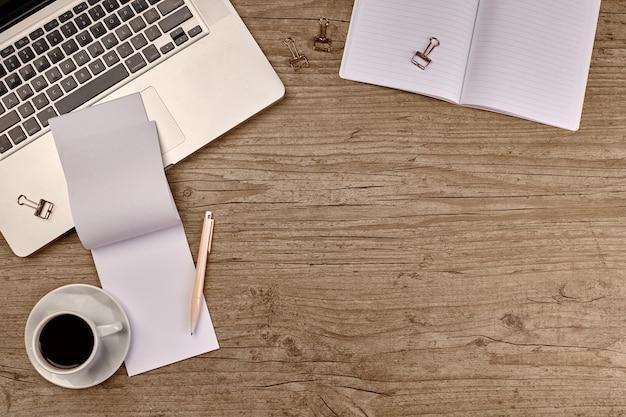 나무 테이블에 용품이 있는 상위 뷰 노트북