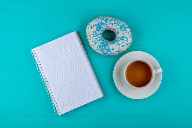 Top view of notebook with sweet donut and a cup of tea on a turquoise surface