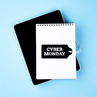 Top view of notebook with tablet and tag for cyber monday