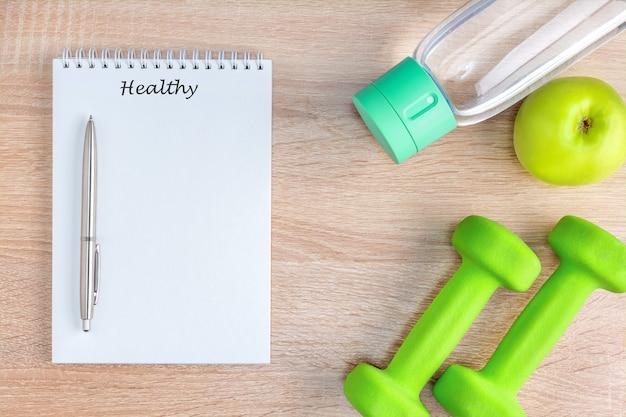 テキストとペン、果物、水、スポーツ用品を備えたトップビューノートブック。健康的なライフスタイルのコンセプト。