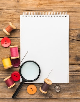 Top view of notebook with thread and magnifying glass