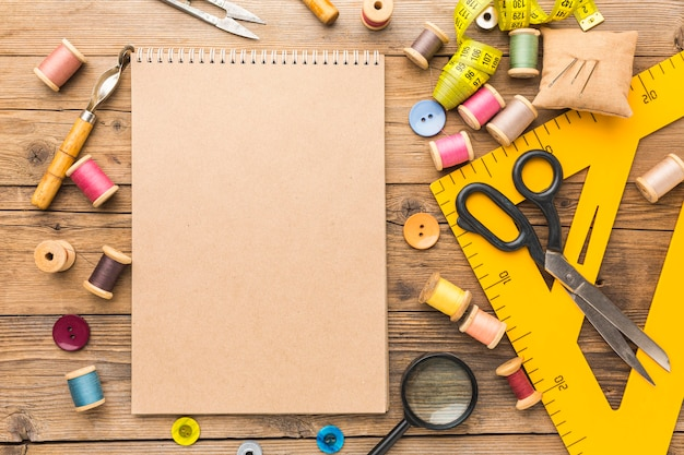 Top view of notebook with thread and scissors