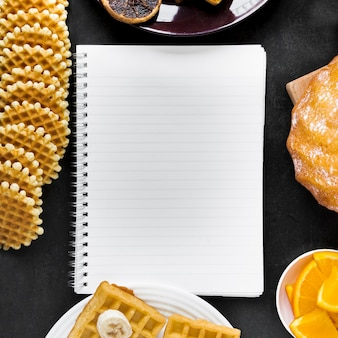 Top view of notebook with waffles and citrus