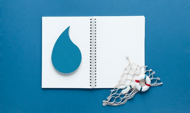 Top view of notebook with water drop and fishing net