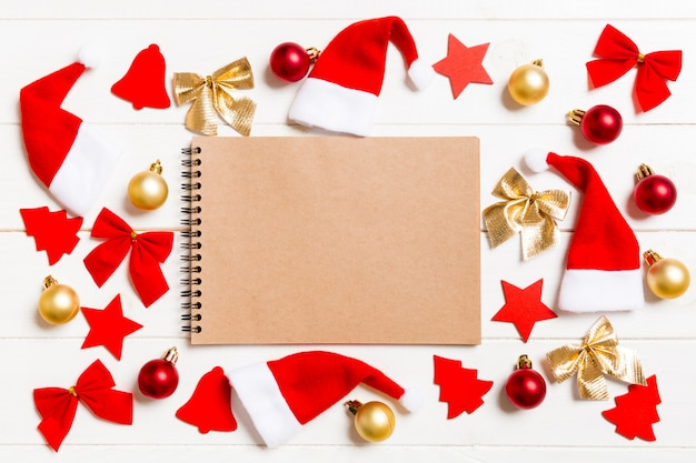 Top view of notebook on wooden background full of christmas decorations