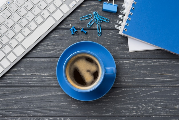 Top view of notebook on wooden desk with coffee cup and paper clips