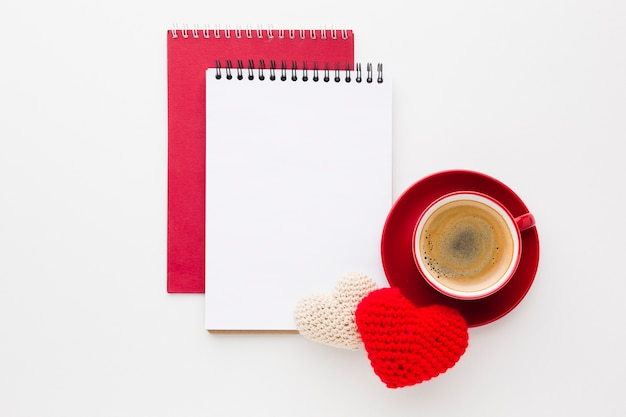 Top view of notebooks and coffee with valentines day ornaments