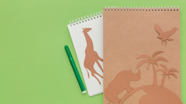 Top view of notebooks with paper animals and copy space for animal day