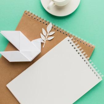 Vista dall'alto di quaderni con colomba di carta