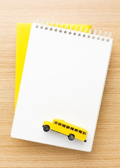 Top view of notebooks with school bus
