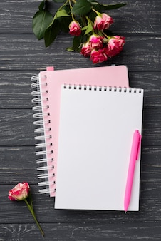 Top view of notebooks on wooden desk with bouquet of roses