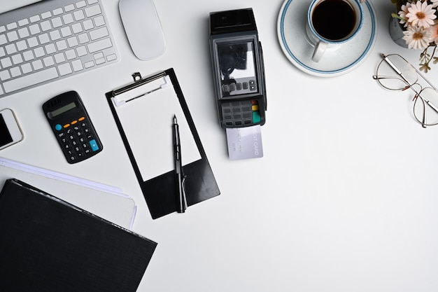 白いテーブルの上面図、メモ帳、電卓、ドキュメント、決済端末。