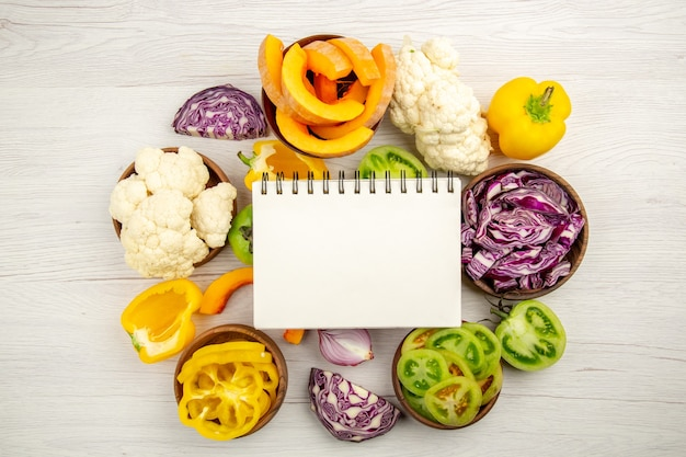 Top view notepad cut green tomatoes cut red cabbage cut pumpkin cauliflower cut bell peppers in bowls on surface