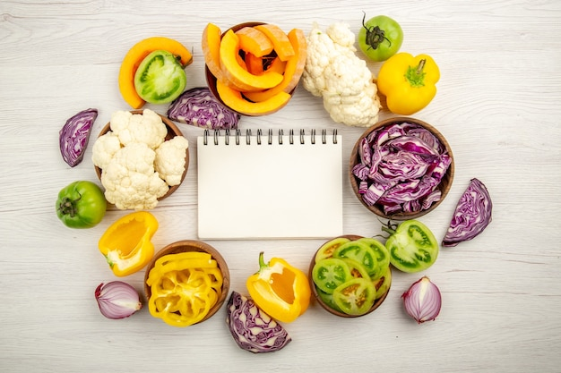 Top view notepad red cabbage cauliflower yellow bell pepper green tomato in bowls on white wooden surface