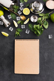 Top view of notepad with cocktail essentials and ice cubes