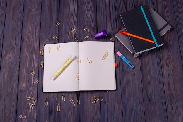 ペンとペーパークリップ付きの上面図のメモ帳。灰色の木の背景。
