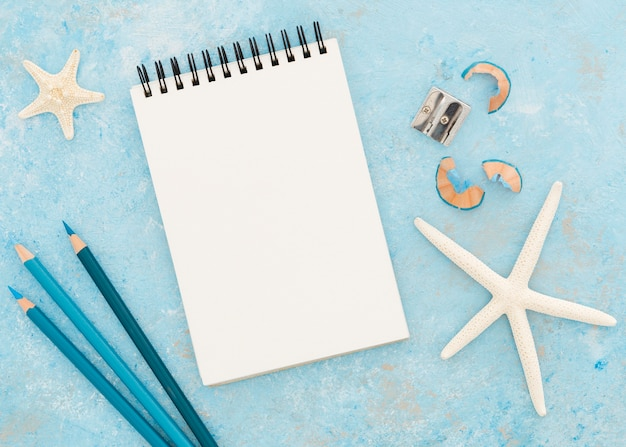 Вид сверху блокнот с карандашами на синем фоне