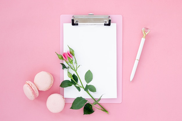 Top view of notepad with rose and macarons
