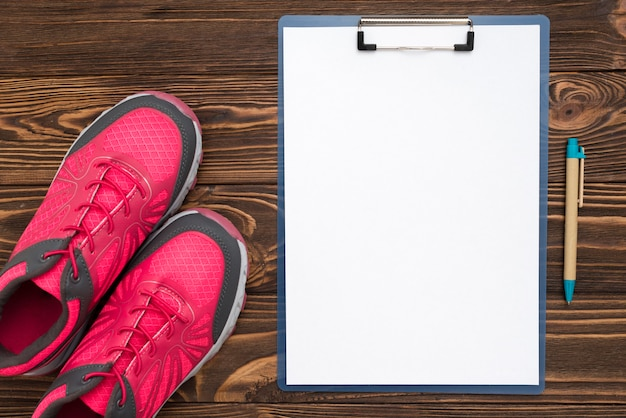 Top view of notepad with sneaker and pen