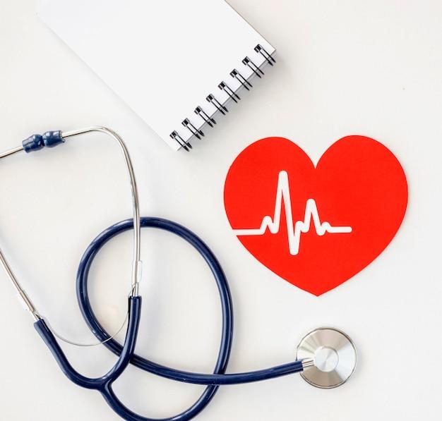 Vista dall'alto del blocco note con lo stetoscopio e il cuore di carta
