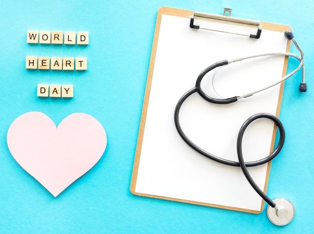 Top view of notepad with stethoscope and paper heart