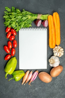 Top view of notepad with vegetables around it on dark grey background