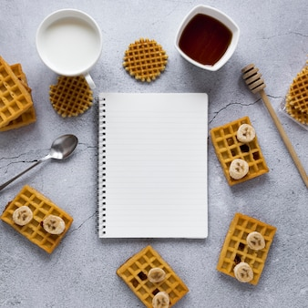 Top view of notepad with waffles and banana