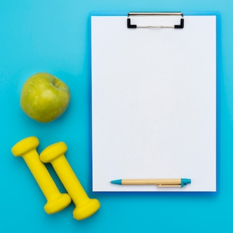 Top view of notepad with weights and apple