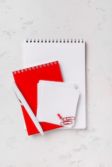 Top view of notepads on desk with pen and sticky notes