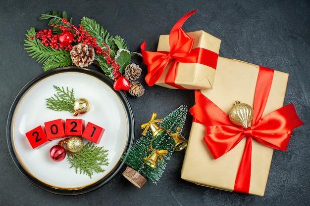 Vista dall'alto di accessori per la decorazione di numeri su un cono di conifere di rami di abete piatto e scatole regalo con nastro rosso a forma di fiocco su sfondo scuro