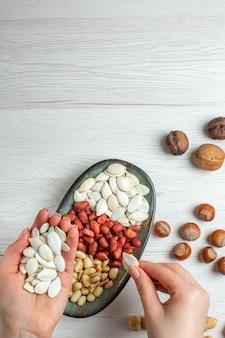 Вид сверху ореховый состав семена арахиса фундук и грецкие орехи на белом столе в женской руке