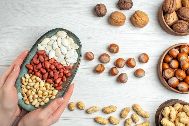 Вид сверху ореховый состав, семена арахиса, фундук и грецкие орехи на белом столе