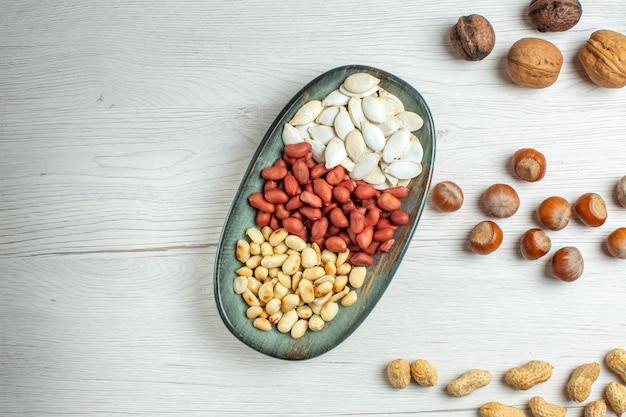 Vista dall'alto composizione di noci semi di arachidi nocciole e noci sul tavolo bianco