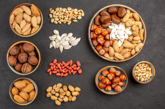 Top view of nut composition with different fresh nuts on a dark surface